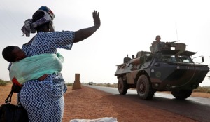 A woman waves to French soldiers heading toward the recently liberated town of Diabaly
