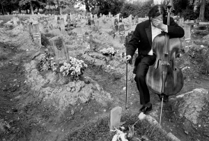 Cellist Vedran Smalovic breaks down in tears after playing a requiem to a dead friend at Hero's Cemetery, where Bosnian fighters were buried during the siege of Sarajevo, 1992